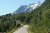 Norweskie wyspy Lofoty - rowerzysta na drodze wśród gór
