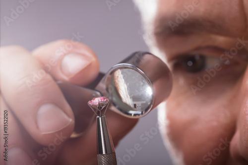 Osoba sprawdzająca diament za pomocą lupy powiększającej
