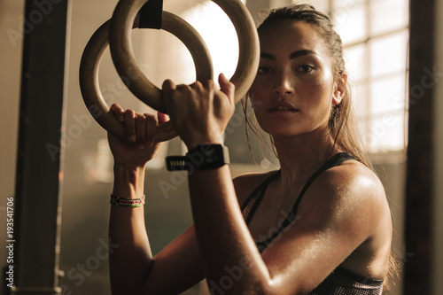 Wall mural Determined woman exercising with gymnastic rings