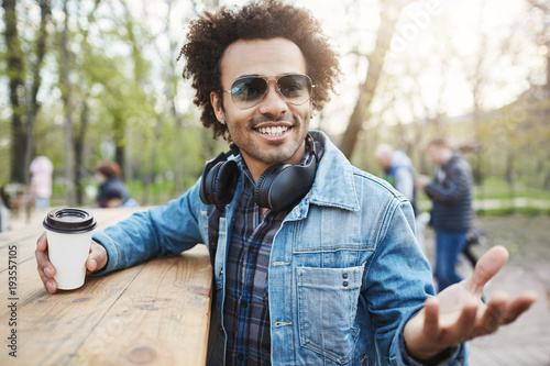 Outdoor shot of fashionable dark-skinned man with afro hairstyle, wearing trendy glasses and headphones over neck, leaning on table in park, drinking coffee and discussing something with gestures.
