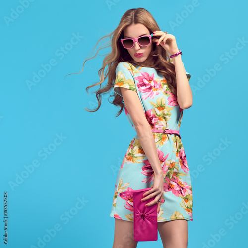 Gorgeous Fashion Blond woman, Trendy Sunglasses. Young female model in Stylish Summer Outfit Posing in Studio. Glamour Long-haired Beautiful Lady. Wavy fashionable Hairstyle