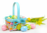A colorful Easter basket full of sparkly eggs in blue, pink, yellow and green with copy space on a bright white background. Shallow depth of field with yellow flowers in the distance. - 193572929