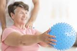 Senior woman exercising with ball