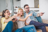 Three friends relax and watch television in bright living room