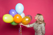 Leinwandbild Motiv Birthday party. Concept of gifts and congratulations. Stylish young smiling beautiful blonde woman in evening dress on a pink background with large multi-colored helium balls.