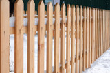 Wooden fence covered with snow around garden in winter time. - 193599934