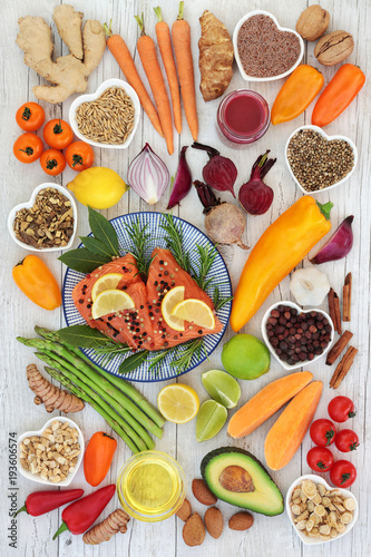 Health food for heart fitness concept with super foods of salmon fish, fruit, vegetables, seeds, nuts, spice and herbs used in herbal medicine and providing omega 3, anthocyanins and antioxidants. © marilyn barbone