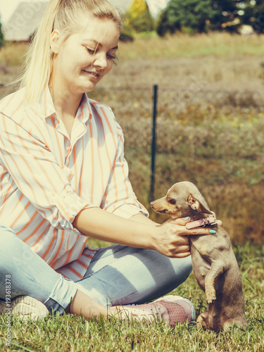 Tuinposter Praag Woman playing with little dog outside