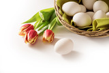fresh easter eggs in a basket and red tulips as a holiday corner background that fades to white, copy space - 193621325