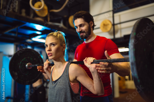 Wall mural Young attractive woman doing exercises with personal trainer.