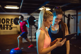 Fototapety Attractive girl using tablet computer in the gym.