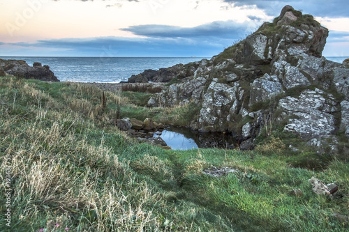 Fotobehang Khaki Beautiful landscape. Rocky beach, blue sky and the sea. Cove Bay, Scotland, United Kingdom. October 2017