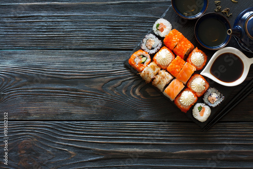 Tuinposter Sushi bar Assorted sushi and tea set served on a black wood table