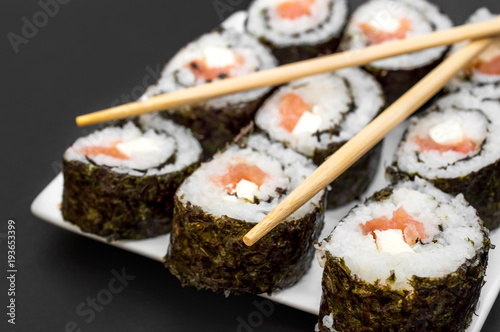 Tuinposter Sushi bar Plate with sushi and chopsticks on a black background.