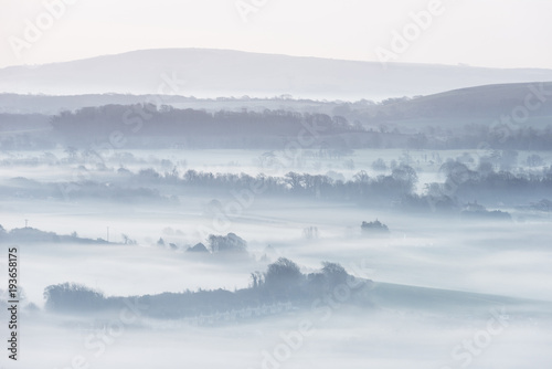 Aluminium Wit Stunning foggy English rural landscape at sunrise in Winter with layers rolling through the fields