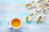 Cup of tea and branches of blossoming apricot on old wooden table. - 193662737
