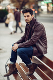 Thoughtful young man sitting on an urban bench. - 193665951