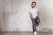Little fashionable boy posing in front of gray concrete wall. Portrait of smiling child in white T-shirt and gray trousers. Concept of style and fashion for children.