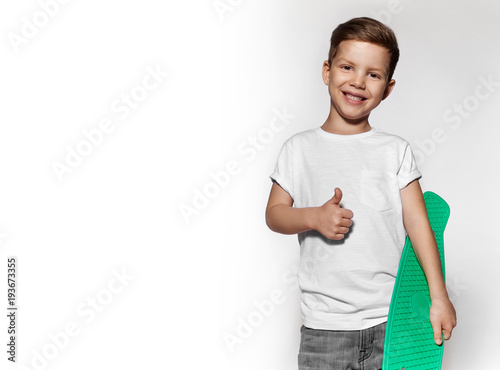 Aluminium Skateboard Cute little boy with skateboard showing gesture thumb up. Concept of sport and positive. Portrait of skater boy, photo isolated on white background. Little guy in white T-shirt with green skateboard.