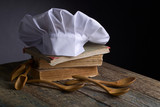Old culinary books , chef hat and wooden spoons . - 193685940