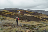 One woman wanders in Iceland with backpack in a red jacket