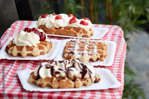 In de dag Wenen Popular national dish Belgian waffles with strawberries, cherries, chocolate and powder in the tourist town of Bruges