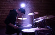 Portrait of immersed and concentrated drummer rehearsing on drums in the studio