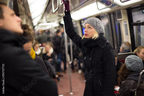 Beautiful blonde caucasian lady wearing winter coat traveling by metro in rush hour. Public transport.