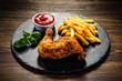 Grilled chicken leg with French fries served on black stone on wooden table - 193708586