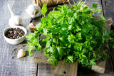 Sprigs of fresh parsley, garlic and various spices on the rustic kitchen table. - 193726739