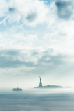 Staten Island Ferry cruises past the Statue of Liberty in dramatic storm. Manhattan, New York City, United States of America. Vertical composition. Copy space. - 193747998