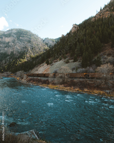 Fotobehang Bergrivier Cargo train along the Colorado River with winter trees and mountainside.