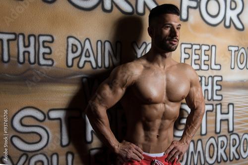 Muscular Man Flexing Muscles At Graffiti Wall