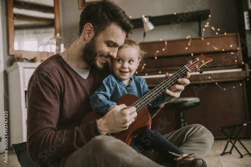 Father teaching daughter to play guitar at home - 193767325