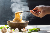 Hand uses chopsticks to pickup tasty noodles with steam and smoke in bowl on wooden background, selective focus - 193770947