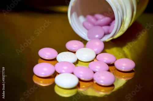 Foto op Aluminium Apotheek Медицина. Витамины в виде таблеток белого и фиолетового цветов рассыпаны на золотом фоне
