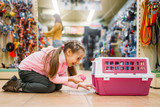 Little girl plays with carrier for cat in pet shop