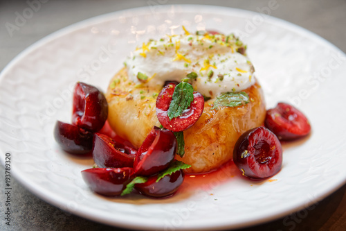 Fotobehang Kersen Grilled peach with cherries and whipped cream