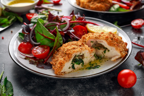 Canvas Kiev Breaded Chicken Kiev breast stuffed with butter, garlic and herbs served with vegetables in a plate.