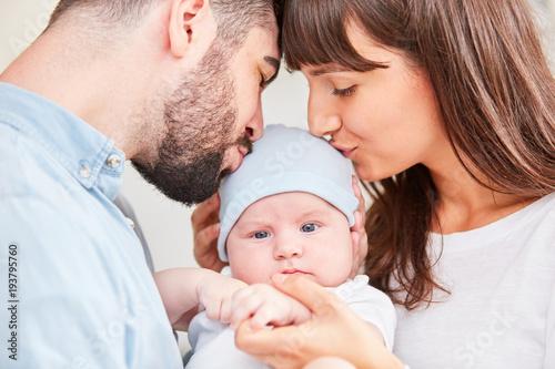 Mutter und Vater küssen Baby auf die Stirn