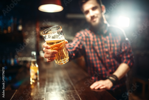 Man holds glass of beer, guy at the bar counter.