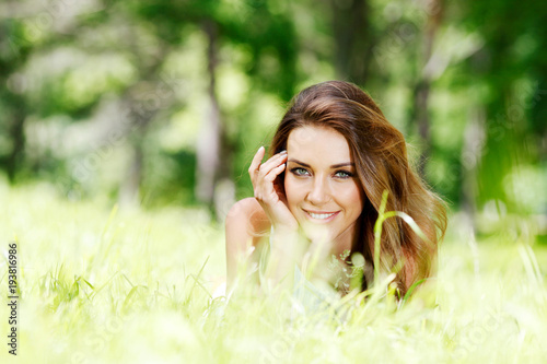 Fototapeta young woman in blue dress lying on grass