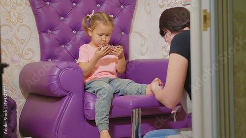 Tuinposter Pedicure Cute baby girl using smart phone at pedicure procedure at beauty spa salon