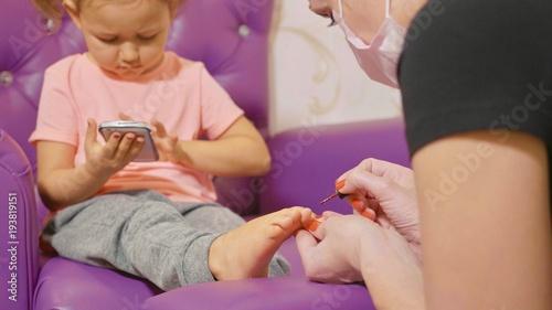 Fotobehang Pedicure Cute baby girl using smart phone at pedicure procedure at beauty spa salon.
