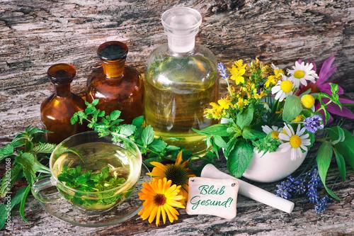Fotobehang Apotheek Kräutertee mit Medizinflaschen und heilenden Kräutern im Mörser. Bleib gesund