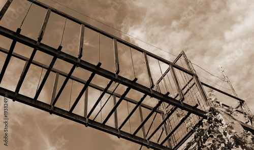 suspended bridge of rusted iron with sepia toned effect