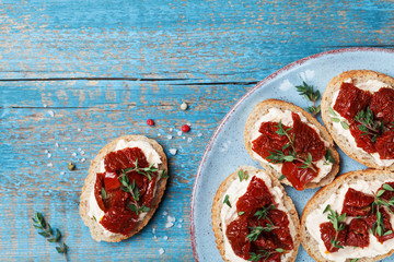 Mediterranean snack or appetizer from bruschetta, cream cheese and sun dried tomatoes. Top view.