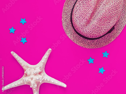 A hat knitted from straw and a large starfish are on a clean purple background. A few blue stars are scattered around. Image for advertisement of travel agency, party banner, rest and holiday - 193835153