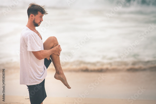 Man surfer stretching and warming up before surfing