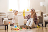 Daughter and mother cleaning home together and having fun. - 193838777